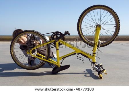 Child fixing his bike - stock photo