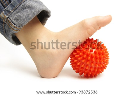 Child foot with spiny plastic orange massage ball on white background - stock photo