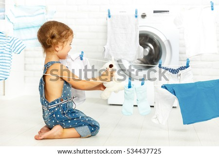 child fun happy little girl to wash clothes and teddy bear in the laundry room