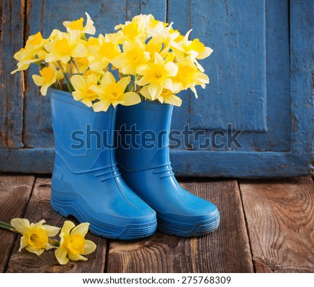 child garden shoes with spring flowers - stock photo