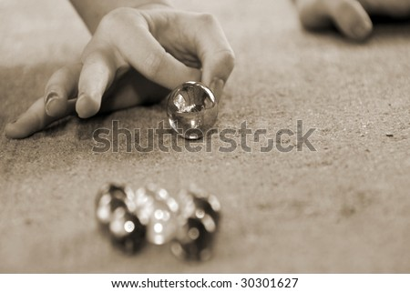 Child getting ready to shoot during marble game - stock photo