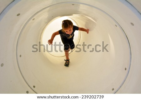 Child (girl age 05) plays in playground tunnel. Concept photo childhood. copy space - stock photo