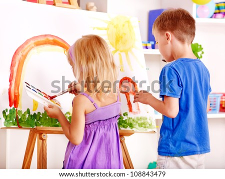 Child girl and boy painting at easel in school. - stock photo