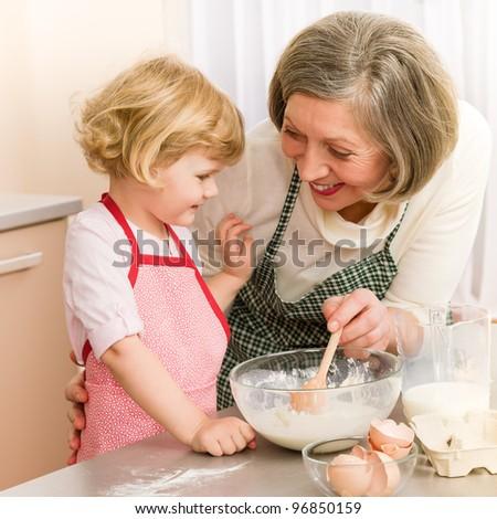 Child girl and grandmother baking cake stir dough - stock photo