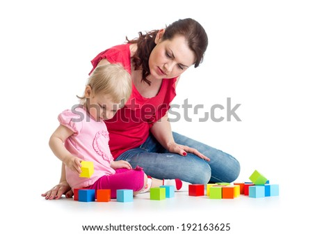 child girl and her mom play with building blocks - stock photo