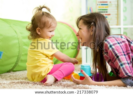 child girl and her mother playing together with toys - stock photo