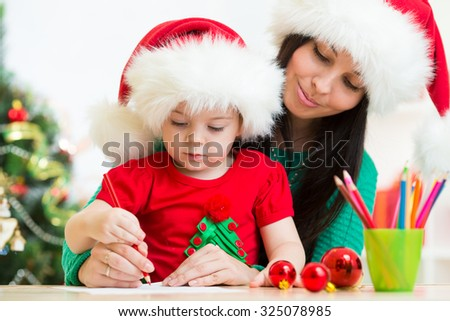 Child girl and her mother writing letter to Santa - stock photo