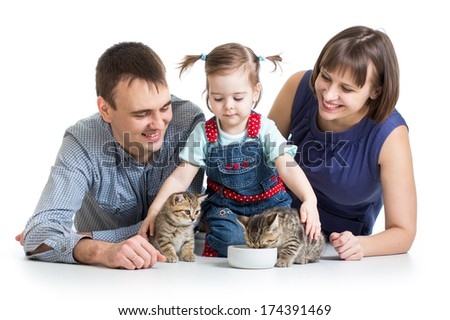 child girl and her parents feeding small kittens - stock photo