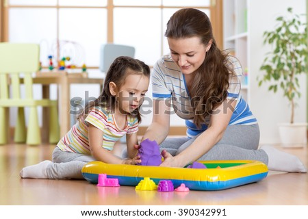 Child girl and mother playing with building toy sand at home - stock photo