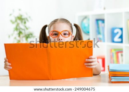 child girl at the table with books at home interior - stock photo