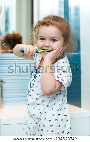 Child girl brushing teeth in bathroom - stock photo