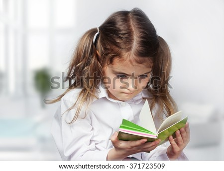 Child girl caucasian concentrated hard learn read note book indoor.Education concept.Hard study. - stock photo