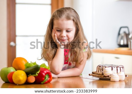 child girl choosing between healthy vegetables and tasty sweets - stock photo