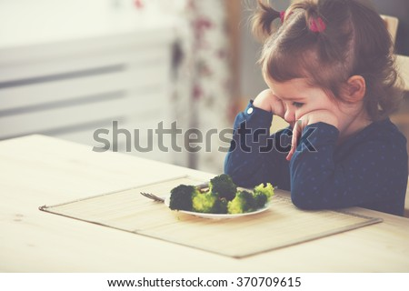 child girl does not like and does not want to eat vegetables - stock photo