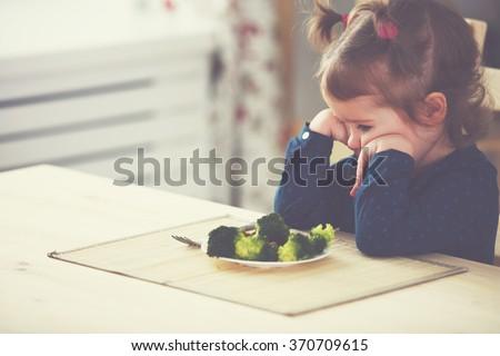 child girl does not like  eat vegetables - stock photo