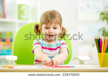 child girl drawing with colourful pencils at home - stock photo