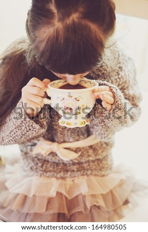 Child girl drinking from a vintage cup of hot drink, sepia tone added - stock photo