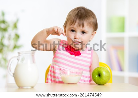 child girl eating food itself with spoon - stock photo