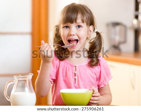 child girl eating healthy food in kitchen