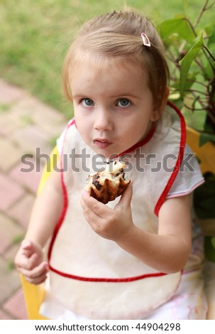 Child girl eating pastry food outdoor - stock photo