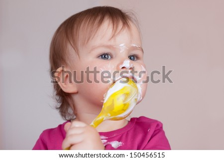 Child girl eating with spoon enjoying her favorite food