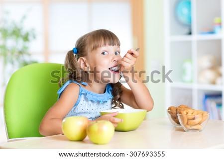Child girl eats tasty breakfast in nursery - stock photo
