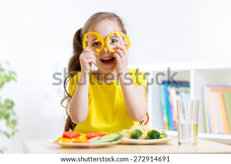child girl eats vegan food having fun in kindergarten - stock photo