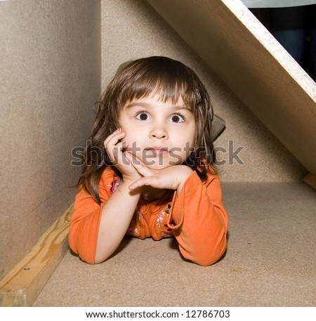 Child girl goggleeyed hiding in wooden box, dreams alone (Victoria, series Children)