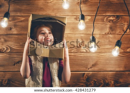 Child girl in an astronaut costume playing and dreaming of becoming a spacemen. - stock photo