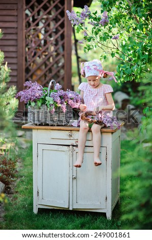 child girl in pink dress in spring garden sitting on vintage bureau with lilacs