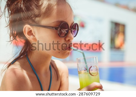 Child girl in the swimming pool with cocktail close-up - stock photo