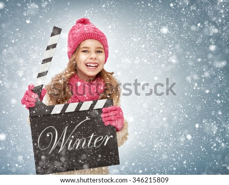 child girl in winter clothes holding clapper board in hands.  - stock photo
