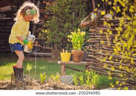child girl in yellow cardigan watering flowers in spring garden - stock photo