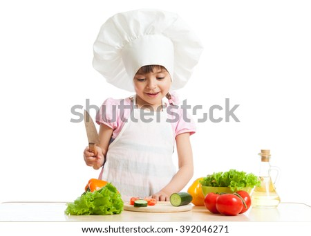 Child girl is cutting vegetables for salad using kitchen knife, isolated over white - stock photo