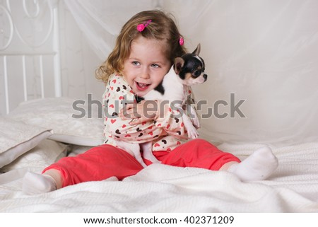 Child girl is sitting on bed at home with dog - stock photo