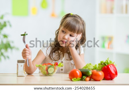 Child girl looks with disgust for healthy food - stock photo