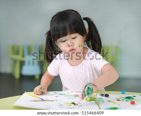 Child girl painting with paintbrush and water colors. Kid activities concept.