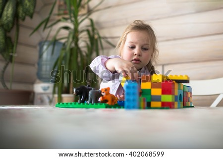 child girl play educational toys in home, little Caucasian girl sisters playing constructor on  table , casual lifestyle photo series in real life interior - stock photo