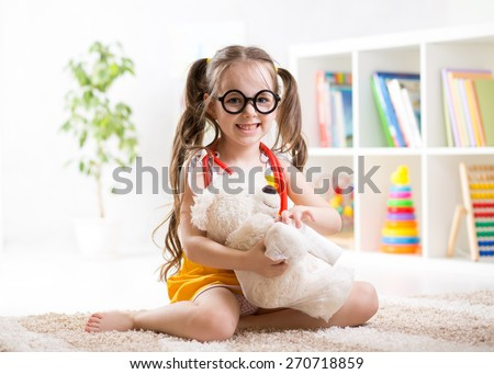 child girl playing doctor and curing plush toy indoors - stock photo