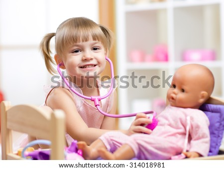 child girl playing doctor role game examinating her doll using stethoscope sitting in playroom at home, school or kindergarten