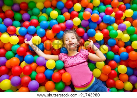 child girl playing on colorful balls playground high view - stock photo