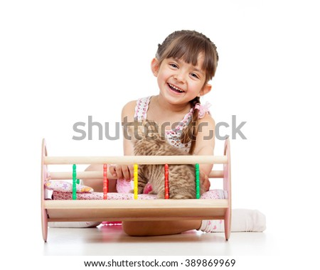 Child girl playing with a kitten and rocking him in doll crib - stock photo