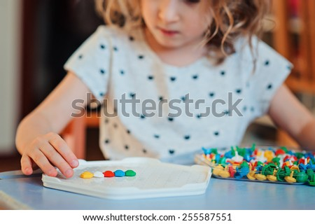 child girl playing with colorful plastic mosaic at home - stock photo