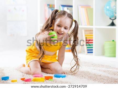 child girl playing with colorful toys at nursery - stock photo