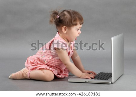Child girl playing with computer on gray background