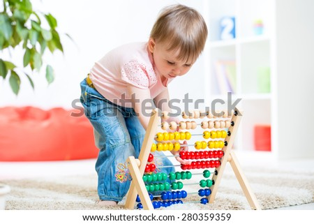 child girl playing with counter toy at nursery - stock photo