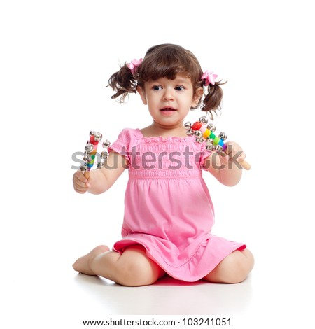 Child girl playing with musical toys. Isolated on white background