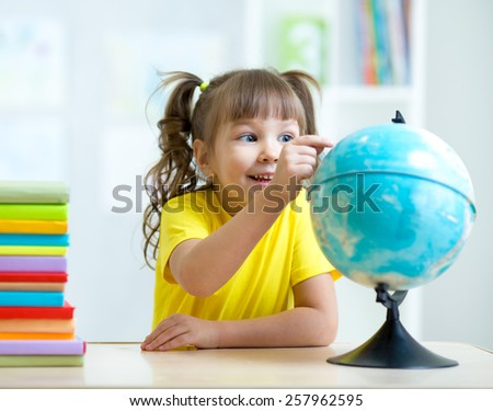 child girl pointing at globe and sitting at table with books - stock photo