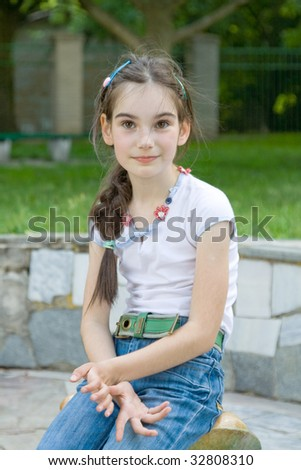 child girl preschool age front portrait green background sits in park - stock photo