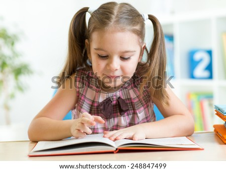 Child girl reading story from big book in nursery